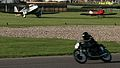 Motorcycle zooms into Madgwick Corner whilst Aircraft wait for take -off Goodwood Revival 2010 (5740630373).jpg