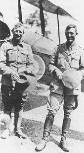 Full-length portrait of two men in military uniforms, standing in front of a biplane