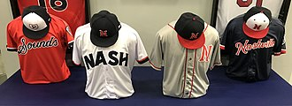 An array of four sets of navy, red, and white baseball jerseys and caps are displayed on a table.