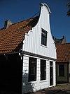 foto van Houten dijkhuis huis met klokgevel (uit- en ingezwenkt voorschot) uit 19de eeuw, houten puntgevel aan de achterzijde voorschot