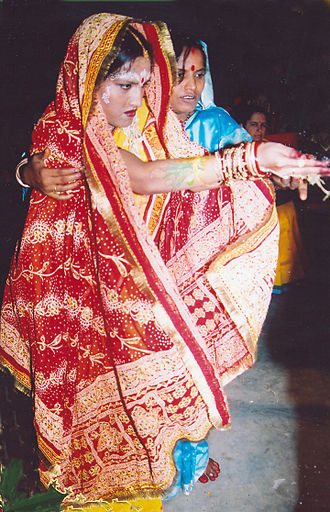 Odia Hindu wedding - an Odia bride offering khai on fire during marriage at the time of Lajja Homa or Khai poda