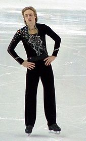 A blond male figure skater dressed in a black suit with glitters moves around on an ice rink.