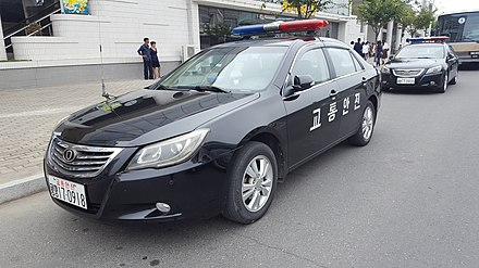 "A North Korean police car in 2017; the Choson'gul lettering on the side translates as ""Traffic safety"". Police car outside Okryu Restaurant.jpg"
