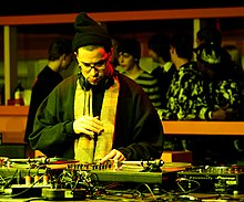 A man wearing eyeglasses, a beanie, scarf, and black sweatshirt, looking down at a set of turntables and other DJ equipment