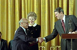 Ronald Reagan shaking hands with Milton Friedman giving him the The Presidential Medal of Freedom