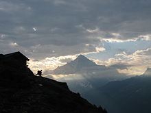 A walker silhouetted by a cabin on mountain slope