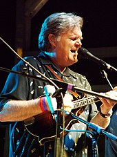 A man wearing a black shirt and playing a stringed instrument with his fingers. His eyes are closed, and he is standing behind microphone stands.