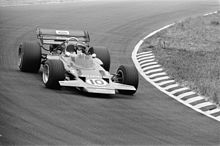 Black-and-white photograph of Rindt racing a flat and winged Formula One car through a corner