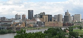 Nearer to the camera, a park area with trees and grass. Behind that is a river which crosses the image. Across the river is a medium-sized downtown with mid- and high-rise building primarily gray and beige in color. The sky is clear with some cloud cover.
