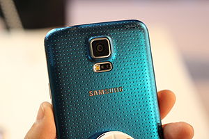 "Samsung Galaxy S5 - Rear of an ""Electric Blue"" Galaxy S5, showing the textured rear, camera, and heart rate sensor."
