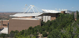 Santa Fe Opera - The Santa Fe Opera's Crosby Theatre viewed from the south showing the unusual roof line and how it is supported. The white, sail-like wind baffles (centre, middle distance) are designed to limit rain from entering the theatre.