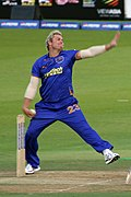 A white coloured man in his bowling action. He is wearing a blue outfit and is alongside cricket stumps. A field and boundary ropes can be seen in the background.