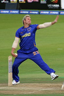 A white coloured man in his bowling action. He is wearing a blue outfit and is alongside the cricket stumps. The boundary ropes can be seen in the background.