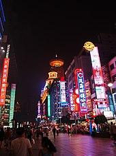 La via pedonale di Nanjing, la sera, guardando verso lo Shimao International Plaza.  Questo è un centro commerciale popolare a Shanghai.