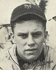 "A man in a baseball uniform with a dark cap with an overlapping ""NY"" on the front looks into the camera."