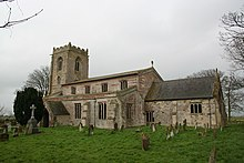 A stone and brick church seen from the southeast showing, from the far end, a battlemented tower, a nave with clerestory, aisle and porch, and a smaller chancel