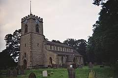 A small church with a square Ashlar tower, in the Early English style. The tower is to the left, the nave to the right, and we are looking somewhat obliquely at it.  The church is ringed by medium size trees, and a large Yew dominates the right of the picture, in the middle distance.  A handful of mismatched gravestones dot the grassy nearground of the picture.