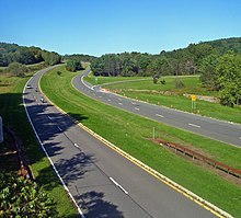 A divided highway with gentle curved roadways receding into a countryside of rolling hills
