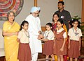 The school children tying 'Rakhi' to the Prime Minister, Dr. Manmohan Singh, on the occasion of 'Raksha Bandhan', in New Delhi on August 13, 2011. Smt. Gursharan Kaur is also seen (1).jpg