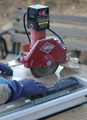 Ceramic tile cutter - A tile saw with a water-cooled diamond blade in use
