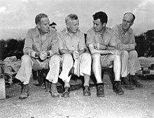 Four men in rumpled fatigues sit on the ground. Tibbets is wearing shorts.