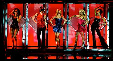 "The Spice Girls performing ""Too Much"" in front of neon pink-coloured, heart-shaped doors in Toronto during The Return of the Spice Girls Tour, February 2008 Toomuchtoronto cropped.jpg"