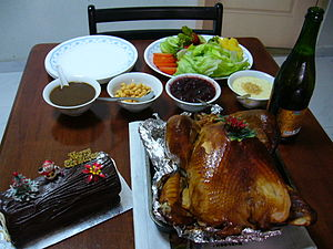 Turkey as food - Roast turkey served with salad, sauces and sparkling juice. On the left is a log cake.
