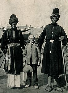 Two Kashmir giants, and their exhibitor, Professor Ricalton. Wellcome V0007379.jpg