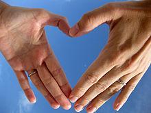 Due mani che creano la forma del cuore, simbolo di amore.