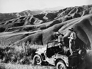 Two men in slouch hats standing in a jeep. They are staring at a series of rugged looking ridge lines