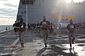 U.S. Marines wear gas masks while participating in a four-mile run during the 2011 Pfc. Ryan M. Jerabek Memorial Challenge on the flight deck aboard the amphibious transport dock USS Green Bay (LPD 20) under way 110820-M-HU586-296.jpg
