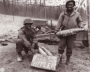 "Field artillery - U.S. Army troops in Europe, winter 1944–45, with artillery shells labeled as ""Easter eggs for Hitler""."