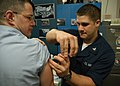 US Navy 060105-N-6060O-015 Hospital Corpsman 3rd Class Matthew D. Petersen, assigned to Strike Fighter Squadron Two (VFA-2), administers a bi-annual Typhoid vaccination.jpg