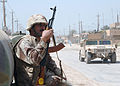 US Navy 060325-N-6901L-039 Iraqi soldier Zatar Jeba sits and watches a U.S. Army patrol drive by in their M1114 HMMWV (Humvee) vehicles during counter-insurgency operations.jpg