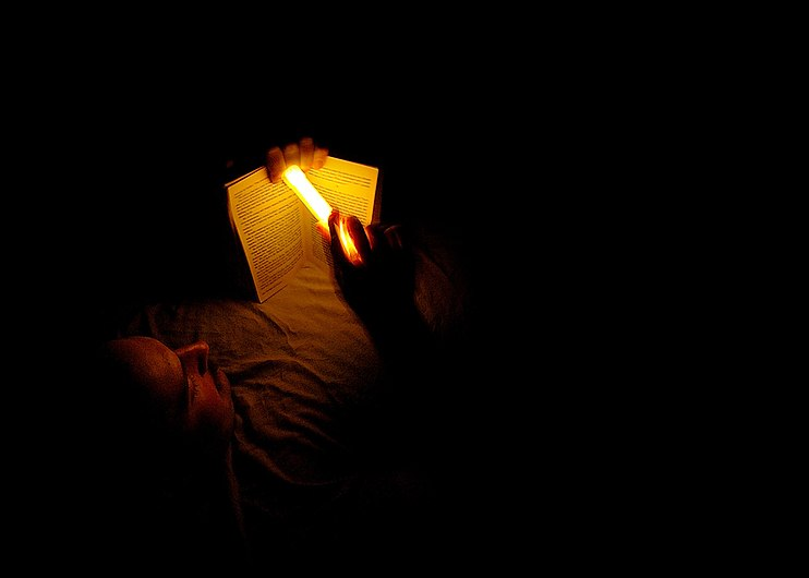 US Navy 060325-N-6901L-137 U.S. Army Staff Sgt. Bradley Cooper reads a book with a chemical light stick, during some down time at a coalition checkpoint in Tarmiya, where ongoing counter-insurgency operations are taking place.jpg