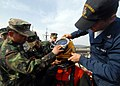 US Navy 070402-N-6936D-022 Navy Diver 3rd Class Nathon Frost assists a Korean navy diver with putting on an MK-17 dive helmet during a combined diving and salvage exercise.jpg