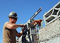 US Navy 081008-N-3560G-416 Builder 3rd Class Robert Russell constructs a block wall while building a bathroom facility.jpg