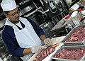 US Navy 091118-N-7478G-162 Culinary Specialist 1st Class Jeffrey Legaspi cuts beef for a Mongolian barbeque meal in the wardroom.jpg