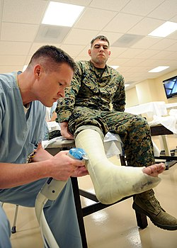 US Navy 100211-N-6326B-126 Naval Medical Center San Diego orthopedic resident Lt. Todd A. Fellers removes a cast from Cpl. Brent R. Wommack in the orthopedic acute care ward.jpg