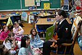 US Navy 100302-N-0718S-004 Cryptologic Technician (Interpretive) 2nd Class Ashlee Russo and her plush cow reads a book by Dr. Seuss to students at George C. Marshall Elementary School.jpg