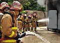 US Navy 100608-N-7643B-280 U.S. Navy Sailors and Coast Guardsmen combat a training fire to demonstrate fire fighting techniques for Royal Malaysian Navy sailors at the Tangkas Fire Training building on the Lumut Naval Base.jpg