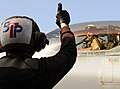 US Navy 120216-N-KQ416-277 Aviation Electrician's Mate Airman Gerad J. Hubbard signals to the pilot of an EA-6B Prowler during startup procedures.jpg