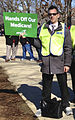 Union member in yellow vest holding AFSCME sign - Hands Off Our Medicare.jpg
