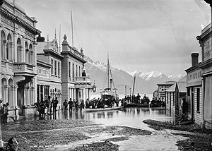 Lewis Hotop - View down Ballarat Street towards Lake Wakatipu following flooding in Queenstown, 1878. Eichardt's Hotel is on the left at the end of the street, and Hotop's chemist shop is across the street on the corner of Rees Street.