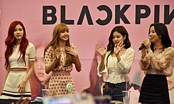 Four members of Blackpink wave against a pink background