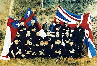1888–89 New Zealand Native football team - The New Zealand Natives before their match against Queensland in July 1889, in front of the United Tribes flag and the Union Jack
