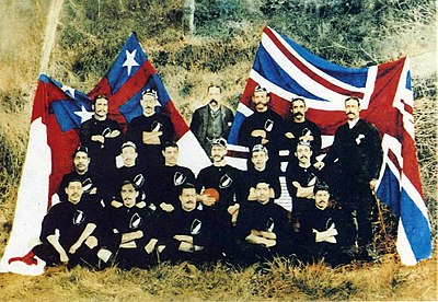 Photograph of the Native football team in their uniform of black shorts and jerseys sat in front of the flags of Great Britain and the United Tribes of New Zealand
