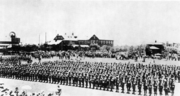 A military unit stands on parade, rifles shouldered, in the middle of a town. Large crowds are gathered around.