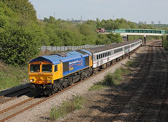 "C F Booth - GBRF Class 66718 ""Gwyneth Dunwoody"" passes Coney Green working 6Z27 Shoeburyness - Rotherham (Booths), consisting of redundant Gatwick Express coaches for scrap"