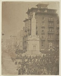 An antique photograph depicting a city square with a stone monument and a large number of soldiers at rest